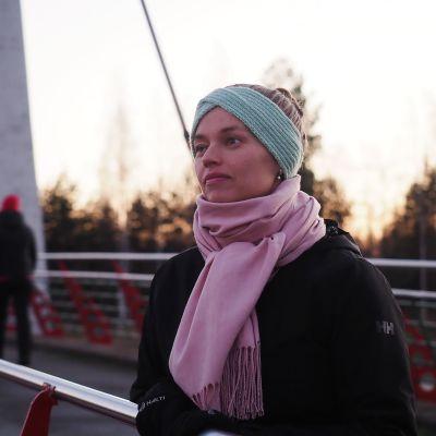 nainen nojaa sillankaiteeseen ja katsoo horisonttiin