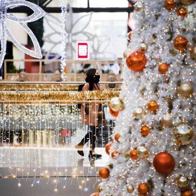 KAsvomaskiin pukeutunut kävelee joulukoristellulla ostoskeskuksessa.