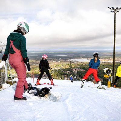 Lumilautailijoita ja laskettelijoita Levin hiihtokeskuksessa.