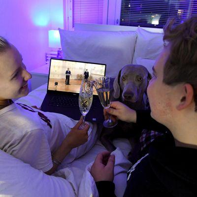 Pariskunta ja koira kippistelee sängyssä ja seuraa itsenäisyyspäivän lähetystä tietokoneelta.
