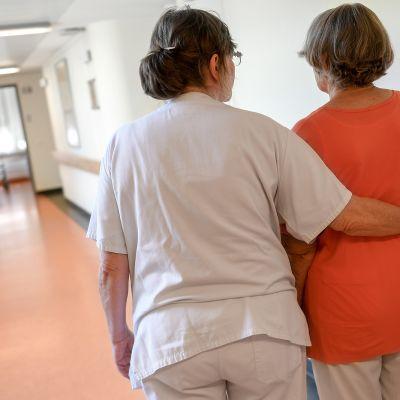 Vanhempi naispuolinen sairaanhoitaja tukee vanhempaa naishenkilöä kävellessä sairaalassa.
