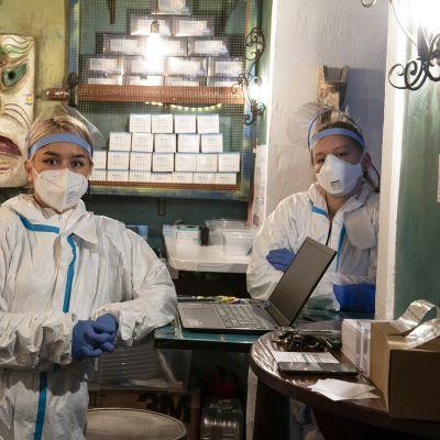 Hoitajat odottavat koronapikatestiin tulijoita tequila-baariin pystytetyllä testiasemalla Frankfurtissa.