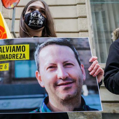 Mielenosoittaja pitää kädessään kuvaa ruotsalaisesta lääkäristä.