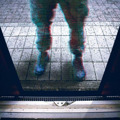 Järjestyksenvalvoja seisomassa junan oviaukon edessä asemalaiturilla.