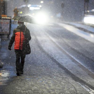 Jalankulkija lumisateessa Hämeentiellä Helsingissä.