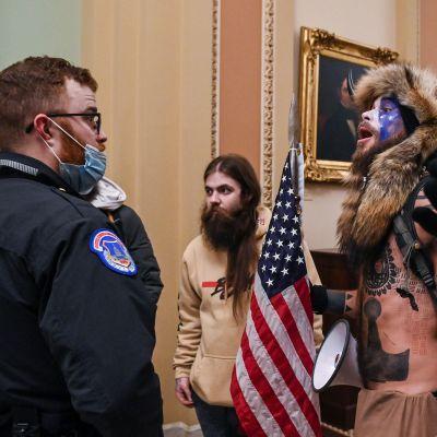 Mielenosoittaja puhuu vartijalle Yhdysvaltain kongressitalossa Washington DC:ssä.