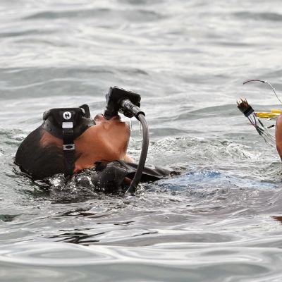 Sukeltaja nostaa lentokoneen osia merestä.