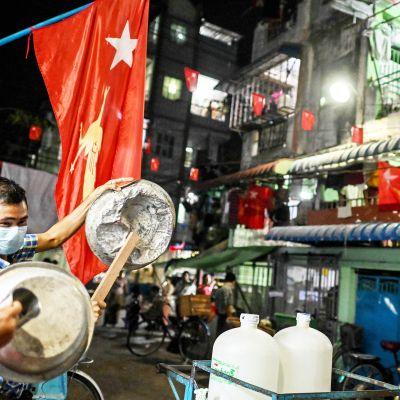Ihmiset paukuttavat peltiastioita Yangonin kadulla.