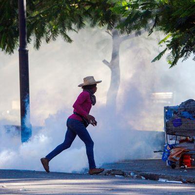 Nainen juoksee pakoon mielenosoitusta Port-au-Princessa, Haitissa.