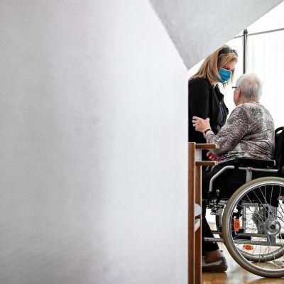 Iäkäs nainen ja hoitaja keskustelevat.