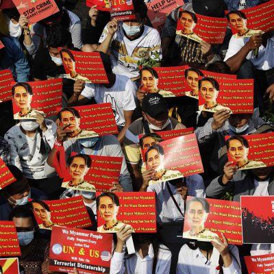 Mielenosoittajat kannattelivat Myanmarin johdosta syrjäytyn Aung San Suu Kyin kuvaa Yangonissa.