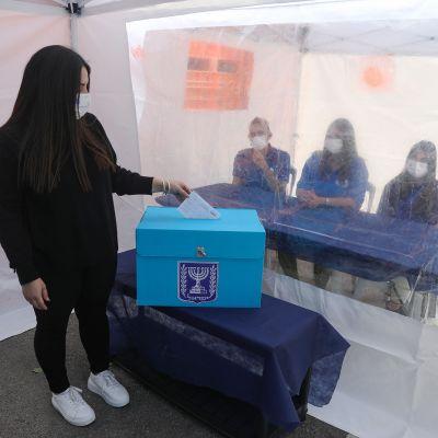 Israelilainen nainen äänestää ja ääntentarkkailijat tarkkailee äänestämistä muovin takaa.