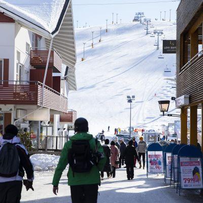 Matkailijoita Levin laskettelu- ja hiihtokeskuksessa Kittilässä aurinkoisena kevättalven päivänä 25. maaliskuuta 2021.