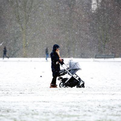 Nainen seisoo lastenvaunujen kanssa lumisateessa.