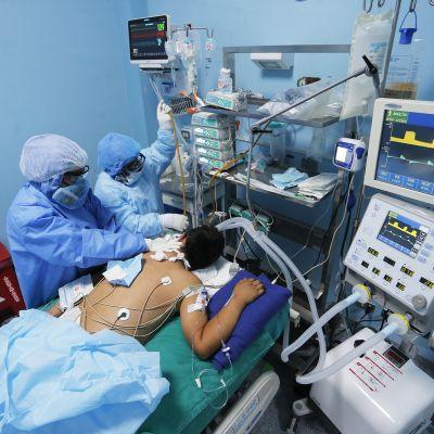 Sairaalahenkilökunta hoitavat potilasta teho-osastolla.