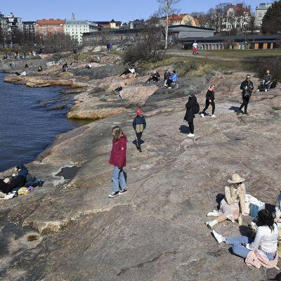 Ihmisiä nauttimassa aurinkoisesta ja lämpimästä kevätsäästä Eiranrannassa Helsingissä