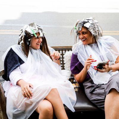 Kaksi naista kadulla raidoitusfoliot päässä kauneuhoitolan edustalla ilman kasvomaskeja.