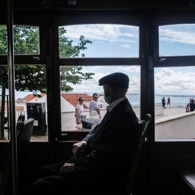 Vanhempi henkilö istuu raitiotievaunussa ja ikunoista näkyy Lissabonin maisemia.