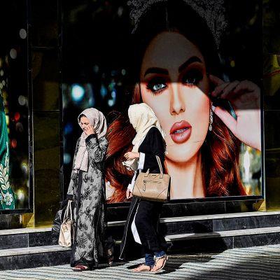 Kaksi afgaaninaista kävelee kadulla  kauneussalongin mainosten edessä.