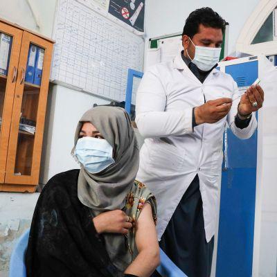 Afganistanilainen naisvanki saamassa Intialaista Astra Zenecan koronarokotetta.
