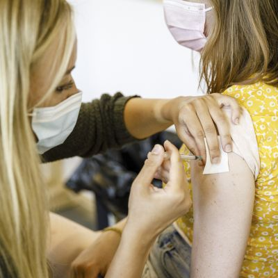 Nuori henkilö saa koronarokotteen Energia-areenan rokotuspisteessä Vantaalla.