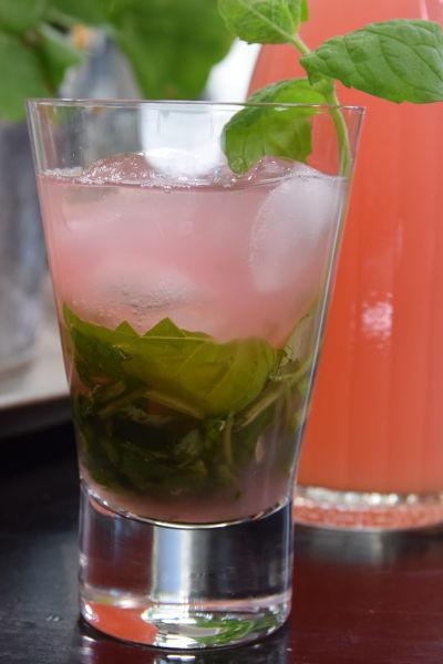 Ett glas med en rosa dryck, gröna örtblad och isbitar. I bakgrunden en flaska med mera rosa dryck.
