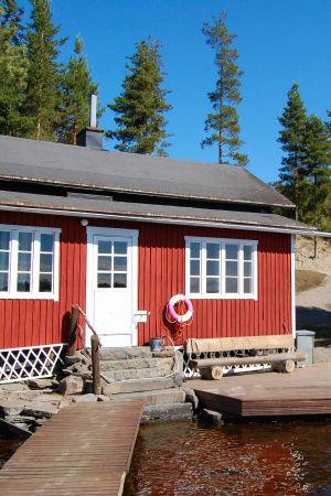 Punainen sauna valkoisilla ikkunankarmeilla seisoo vesistön ja laitureiden edessä.