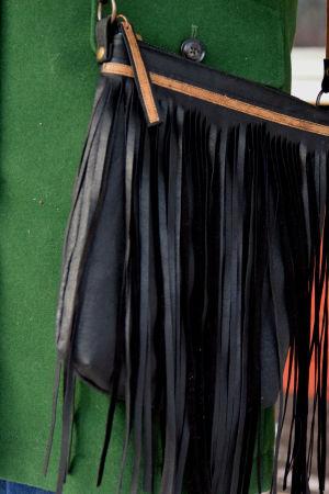 En svart läderhandväska med fransar som hänger mot en grön yllekappa.