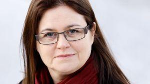 En mörkhårig kvinna med glasögon.