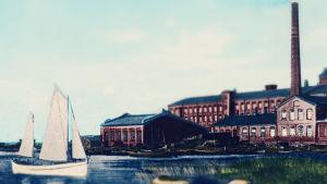 En illustration av en vit skuta som seglar i havet framför Vasa bomullsfabrik i början av 1900-talet.