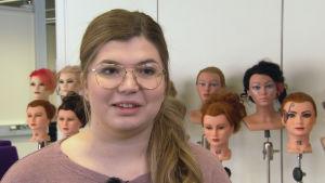 Ung kvinnlig frisörstuderande står framför modelldockor
