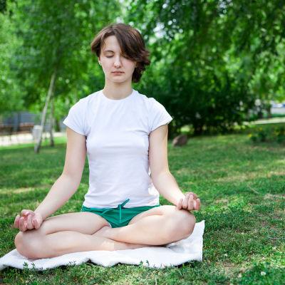 Flicka som mediterar i park.