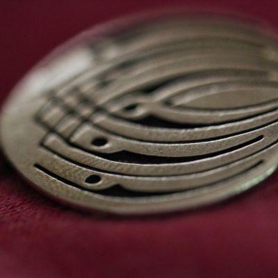 Ett smycke med Prometheus logo.
