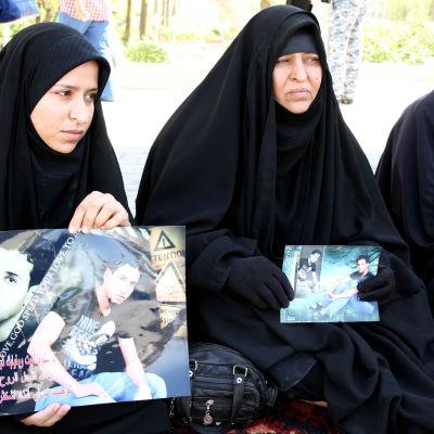 Irakiska kvinnor håller upp bilder på sina anhöriga som mördades i Speicher-massakern i juni 2014.