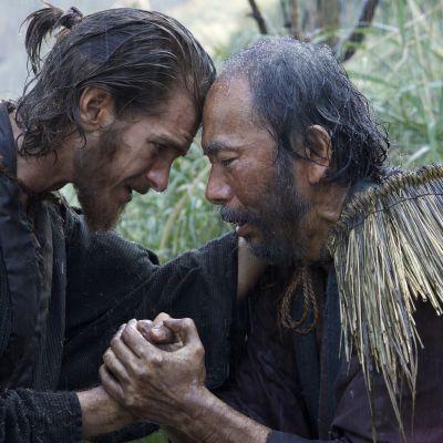 Prästen Rodrigues och bybon Mokichi stöder varandra.