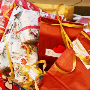 Närbild på julklappar inpaketerade i rött papper och i ljust papper med tomtar på.