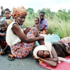 Bild på personer som sitter och ligger längsmed en vägkant.