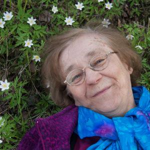 vanha nainen lepää valkovuokkojen keskellä