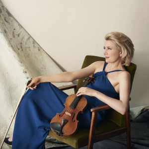 viulisti Elina Vähälä istuu viulukädessä tuolissa