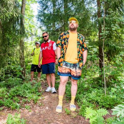 Rap-ryhmä Teflon Brothers kävelee metsäpolulla kesävaatteissa.