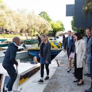 Noin kuuden hengen seurue on Venetsiassa laiturilla siirtymässä veneeseen.