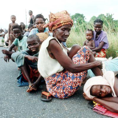 Vaatimattomasti varustautuneita pakolaisia liberialaisen tien varressa.