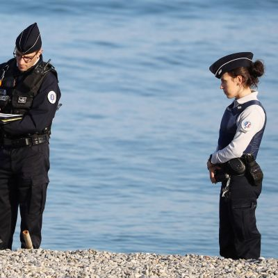 Poliisit kirjoittavat sakkolappua rannalla istuvalle miehelle Ranskan Rivieralla.