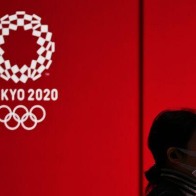 Nainen käyttää hengityssuojainta ja kävelee Tokio2020-seinän ohi.