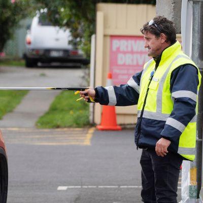 Vartija ojentaa vierailijalle hengityssuojaimen pitkän kepin avulla Wellingtonissa.