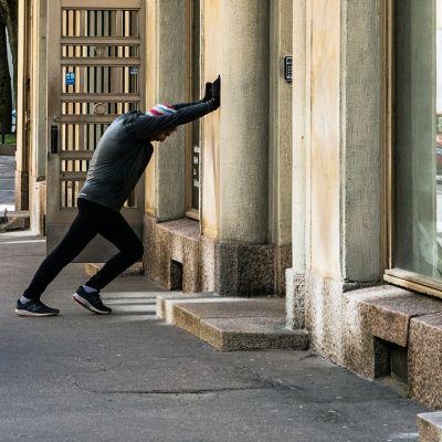 Mies venyttää pohkeitaan kadulla kerrostalontalon seinään nojaten.