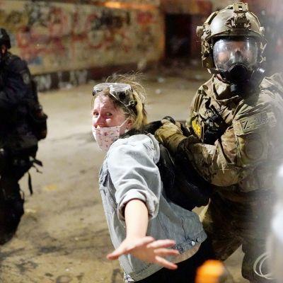 Mellakkavarusteisiin pukeutunut liittovaltion viranomainen pitelee kiinni mielenosoittajasta.
