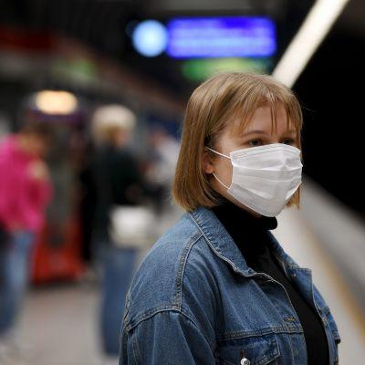 Hengityssuojainta käyttävä nainen Ruoholahden metroasemalla.