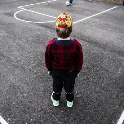 Lapsi seisoo yksin koulun pihalla.