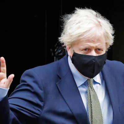 Boris Johnson poistumassa Lontoon Downing Streetiltä maski kasvoillaan.